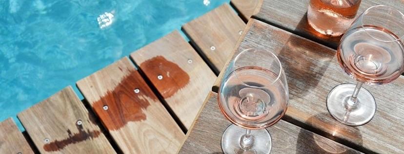 verre de rosé au bord d'une piscine avec trace de pied mouillé